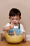 Toddler Baking. Happy young boy stirring cake mixture with a wooden spoon stock photography