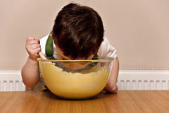 Toddler Baking. Happy young boy stirring cake mixture in a bowl using a wooden spoon and sticking his head inside it royalty free stock photography