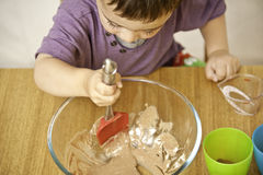 Toddler baking. Picture of a happy young toddler mixing ingredients into a bowl royalty free stock photo