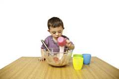 Toddler Baking. PIcture of a happy young toddler mixing ingredients into a bowl isolated on a white background royalty free stock photo