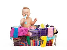 Toddler in basket with clothes. Happy toddler sitting in basket with clothes stock image