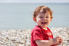 Toddler on beach. One year old boy sitting on a beach on a sunny day Stock Photography