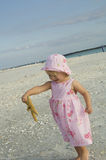 Toddler on beach. Cute toddler on beach looking at starfish wearing sunhat Stock Photos