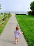 Toddler on Beach Path. Toddler walking on sidewalk toward beach Royalty Free Stock Photography