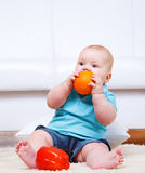 Toddler biting an orange Stock Photos