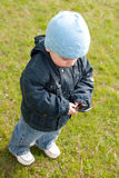 Toddler in blue sending SMS over the mobile Stock Photos