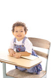 Toddler with a book sitting in desk Stock Photo