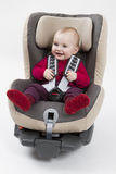 Toddler in booster seat for a car in light background Royalty Free Stock Image