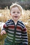 Toddler boy. Blonde, blue eyed toddler boy wearing striped sweater smiling standing in field Royalty Free Stock Photos