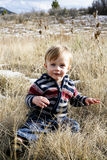 Toddler boy. Blonde, blue eyed toddler boy wearing striped sweater smiling sitting in field Royalty Free Stock Photography