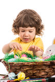 Toddler boy arrange Easter eggs in basket Stock Images