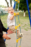 Toddler boy ascending rope ladder outdoors Stock Photo