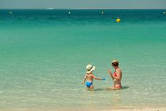 Toddler boy on beach with mother. Two year old toddler boy on beach with mother Stock Images