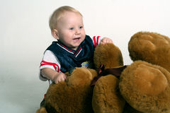 Toddler Boy and Big Teddy Bear. Happy toddler boy with a large, brown teddy bear royalty free stock image