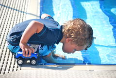 Toddler boy blowing bubbles in a pool. Toddler boy wearing blue blowing bubbles in a pool testing the water for the first time with his toy truck royalty free stock photography