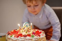 Toddler boy blowing candles on his 2 birthday cake Stock Photography