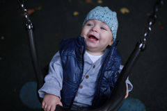 Toddler boy with blue cap laughing on swing looking up. Childhood. Stock Photos