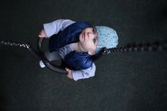 Toddler boy with blue cap on swing looking up. Childhood. Stock Photo
