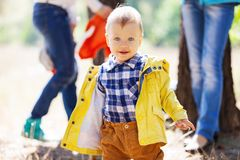 Toddler boy with blurred adults in the background Stock Photo