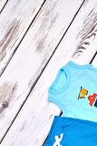 Toddler boy brand summer clothes. Baby boy summer fashion garment, copy space. Infant boy shorts and t-shirt, top view royalty free stock photo