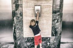 Toddler boy calling elevator button Royalty Free Stock Image
