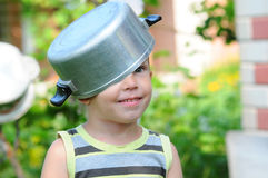 Toddler boy in child with a saucepan. a child with a saucepan on his head. Happy child indulges. royalty free stock photography