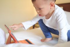 toddler boy child sitting in bed playing with tablet pc stock photo