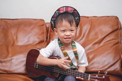 Toddler boy child wearing hat hold & play Hawaiian guitar or ukulele in living room at home. Cute happy smiling little Asian 2 - 3 years old toddler baby boy royalty free stock photo