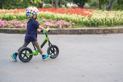 Toddler boy child wearing safety helmet learning to ride first balance bike. Cute little 2 - 3 years old toddler boy child wearing safety helmet learning to ride royalty free stock photos