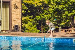 The Toddler boy cleans the pool and pulls the ball out of the po royalty free stock image