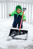 Toddler boy clearing snow Stock Images