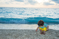 Toddler boy collect pebbles at sea. Toddler boy with curly hair collect little pebbles on beach in front of sea water at sunset royalty free stock image