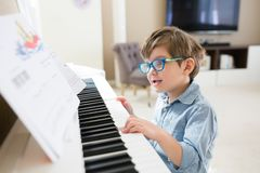 Toddler boy is concentrated on piano and musical notes royalty free stock photo
