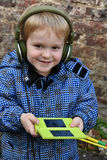Toddler boy with console game. Toddler boy playing with his console game, wearing headphones Royalty Free Stock Images