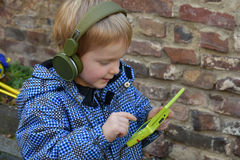 Toddler boy with console game. Toddler boy playing with his console game, wearing headphones Stock Image