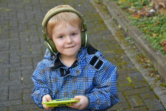 Toddler boy with console game. Toddler boy playing with his console game, wearing headphones Stock Photos