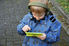 Toddler boy with console game. Toddler boy playing with his console game, wearing headphones Royalty Free Stock Photography