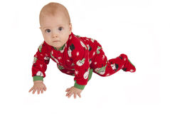 Toddler boy crawling in fleece holiday pajamas Stock Photos