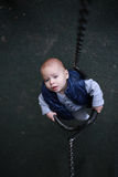 Toddler boy curious on swing looking up. Childhood. Stock Images