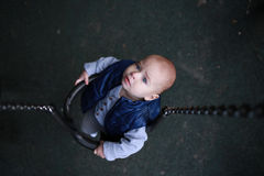 Toddler boy curious on swing looking up. Childhood. Royalty Free Stock Photography