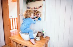 Toddler boy in a dangerous situation in the bathroom. Cute toddler brushing his teeth in the bathroom. Little boy sitting on a sink. Domestic accident Stock Photos