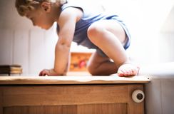 Toddler boy in a dangerous situation in the bathroom. Little toddler boy climbing on a bathroom furniture. Domestic accident. Dangerous situation at home Stock Photos