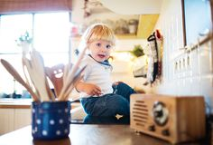 Toddler boy in dangerous situation at home. Child safety concept. Royalty Free Stock Photo