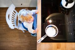 Toddler boy in dangerous situation at home. Child safety concept. Toddler boy in a dangerous situation at home. Domestic accident. Child safety concept. Top Royalty Free Stock Images