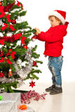 Toddler boy decorate Xmas tree Royalty Free Stock Images