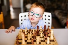 Toddler boy with down syndrome with big blue glasses playing chess in kindergarten royalty free stock photography