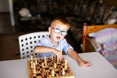 Toddler boy with down syndrome with big blue glasses playing chess in kindergarten stock image