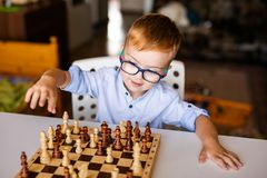Toddler boy with down syndrome with big blue glasses playing chess in kindergarten royalty free stock photo