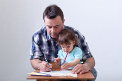 Toddler boy drawing with his father. Toddler boy drawing with colored pencils aided by his father Royalty Free Stock Photos
