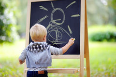 Toddler boy drawing standing by a blackboard Stock Photography